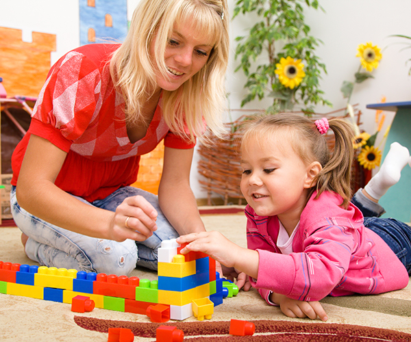 Early Years Teacher Playing Lego Bricks With Young Child