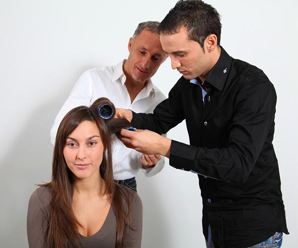 Hairdressing Assessor watching man drying model's hair