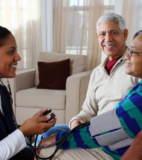 Healthcare Worker With Stethoscope And Elderly Couple