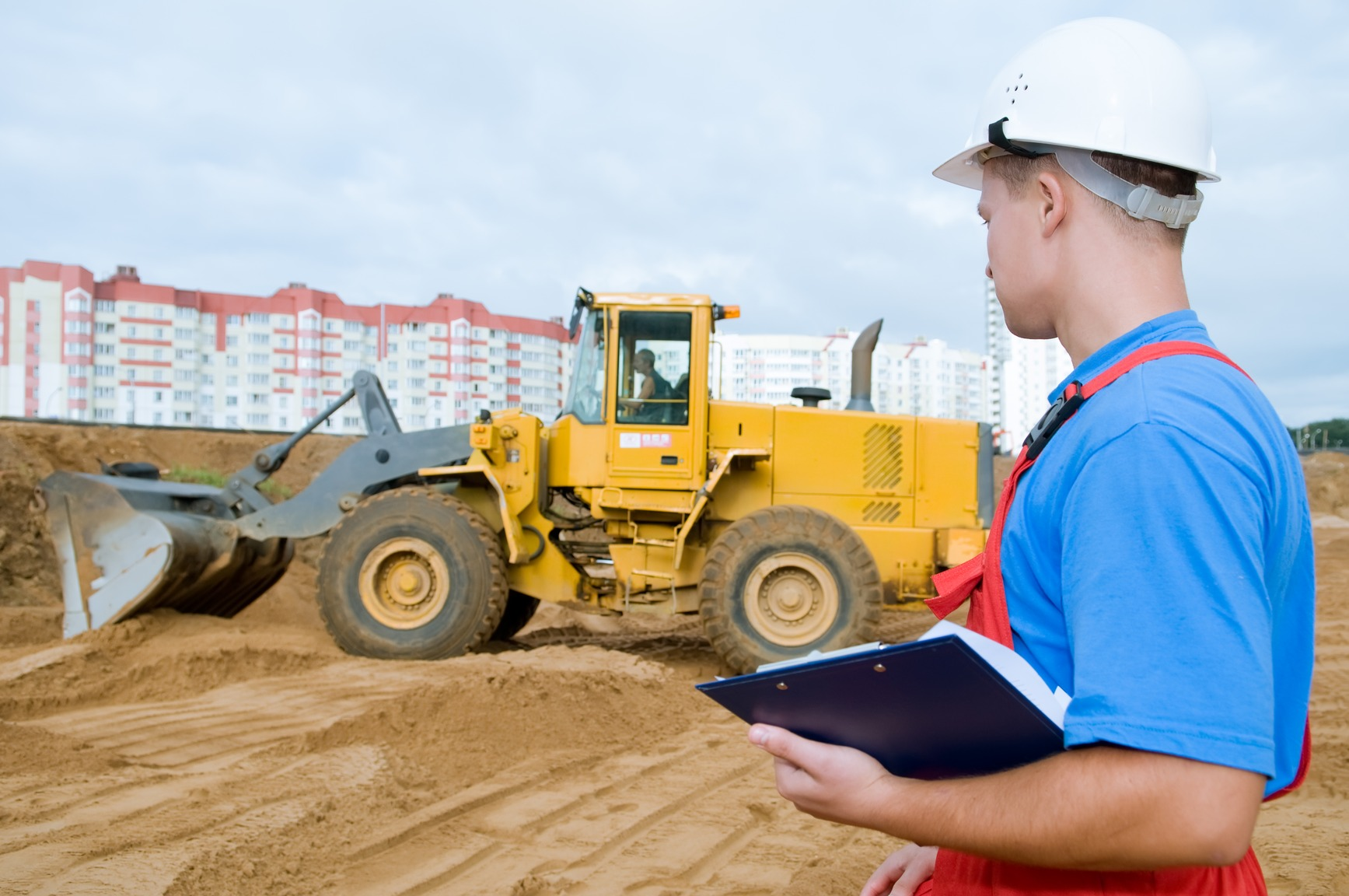 Construction Worker With Clipboard Assessing Digger Driver