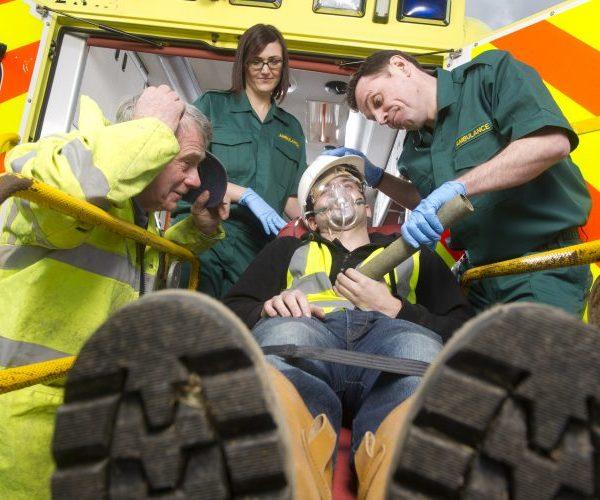 Paramedics helping injured construction worker