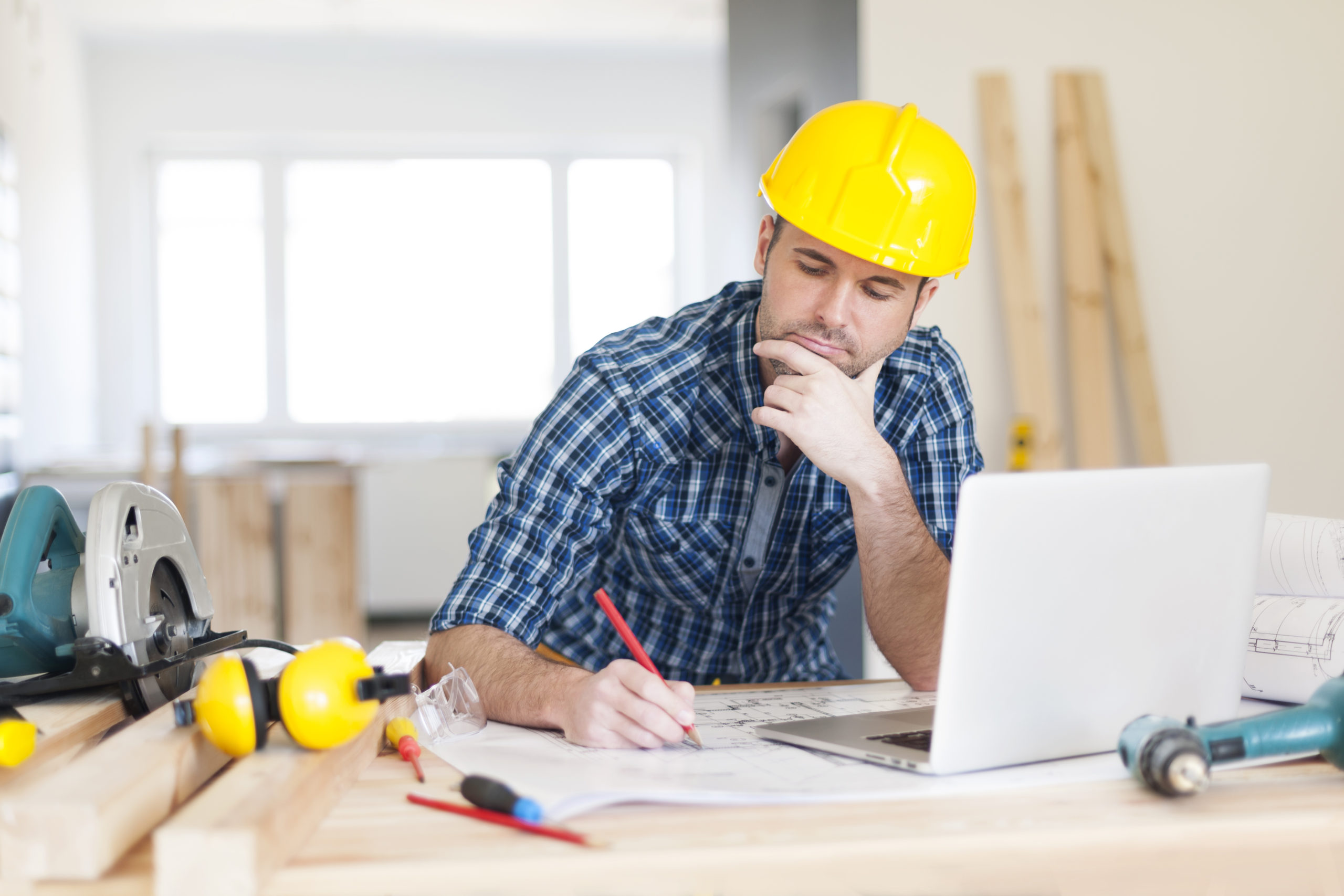 Construction Worker At Desk With Computer