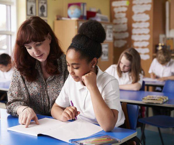 Teacher Helping Child With School Work